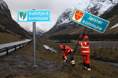 Her blir skiltet på E39 gjennom Våtedalen sett opp. Sunnfjord kommune-skilta står tildekka av plast fram til dei skal avdukast 30. desember klokka 12.