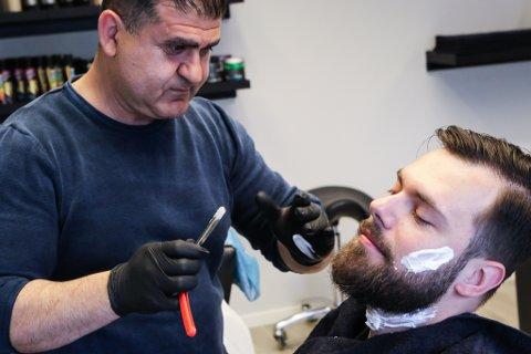 BARBERING: Cetin Nuay (t.v.) er utdanna barberar i Tyrkia. No opnar han barbersalong i Florø sentrum. Her er Damian Kowalik under kniven.