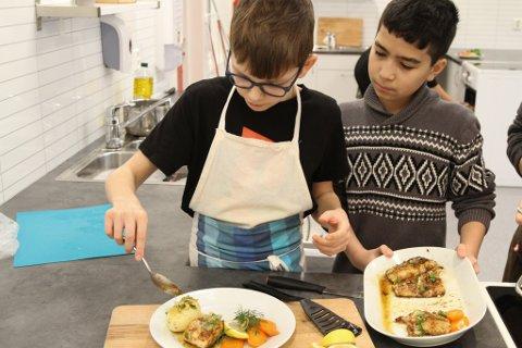 KOKKAR: 6. klasse på Krokane skule deltek i konkurransen Klimakokkane. August Takle Sandal og Kevin Mendill Jakobsen legg opp smørsteikt torsk med grønnsaker.