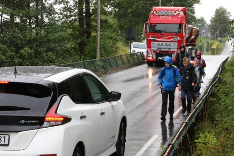 SMALT: Dagleg passerer det store lastebilar på den smale vegen. I møte med skuleelevar og bil er det lite plass å gjere av seg. Bildet er arrangert for å synleggjere trafikkfarlege situasjonar som kan oppstå.