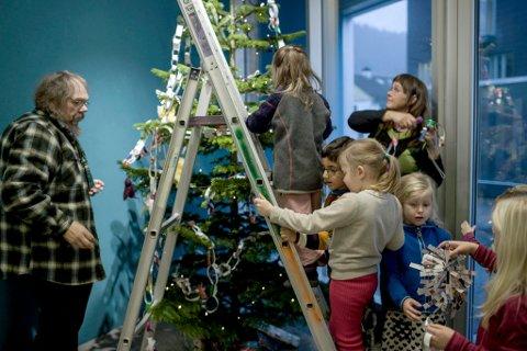 Born frå Hatlehaugen barnehage henger opp sjølvlaga julepynt på juletreet til Førde kunstmuseum.