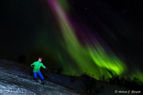 Kjetil Dale i fin driv nedover, medan nordlyset teiknar ei perfekt ramme på skituren.
