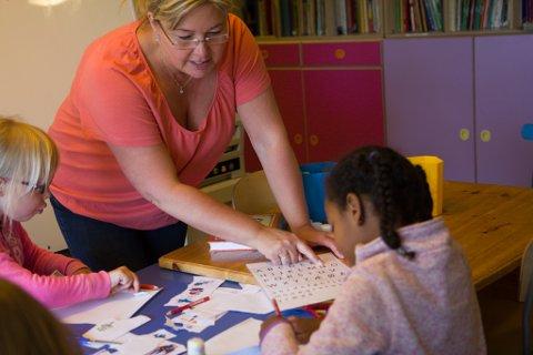 Pedagog Elin Aasheim hjelper Linn Kristin Ekreskar og Deka Abdulahi med skriblinga. Ifølge forskar Hilde Hofslundsengen, gir dette borna eit fortrinn når dei skal lære seg å lese.