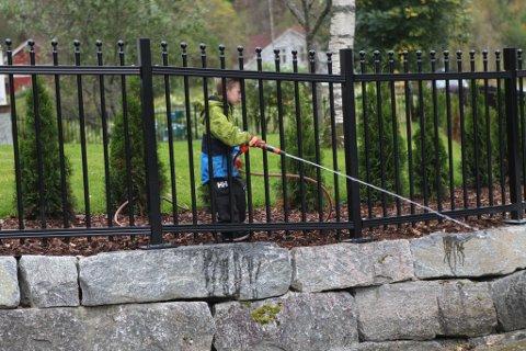 Ungguten Casper Tenold Hjelmeland gjer også sitt beste for å spyle vekk gylla som renn forbi huset.