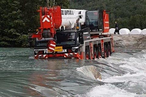 UVANLEG SYN: Her køyrer ein av mobilkranane over elva for å nå kraftverket. Videoen av kryssinga (som du kan sjå i saka) er sett nær 100.000 gongar.