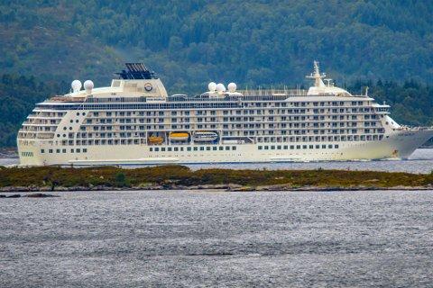 FLATØYA: Dette bildet viser Flatøya utanfor Askvoll i framgunnen, medan eit cruiseskip passerar. Øya er lita og som namnet seier, flat.