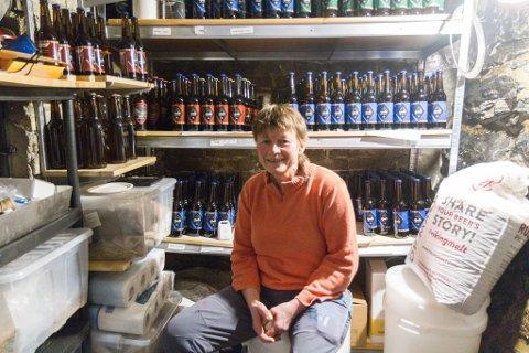 BRYGGEBESTEMOR: Siw-Ingunn Hjelle Eide (57) har starta mikrobryggeriet «Hjelle Gardsbryggeri». Ho har laga tre ulike sortar og fleire skal det bli. Her sit ho på eit lagerrom kor ho lagrar ølflaskene.
