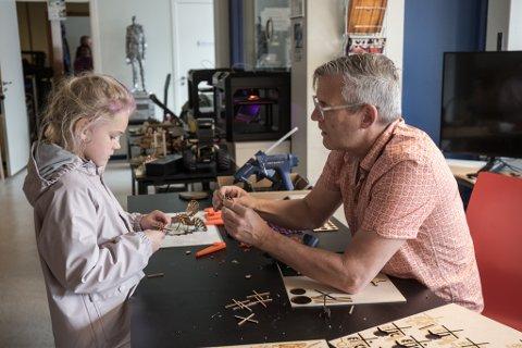 FÅR HJELP: Emma Selnes Øren (6) bygger eit helikopter med delar frå laserkutter i lag med Daniel Longfellow.