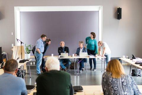 VANSKELEG: Mykje var uavklart før torsdagens kommunestyremøte i Naustdal. Tal og vurderingar vart skrivne på fram til siste frist og vel så det. Her diskuterer dei framleis, ein halv time etter at møtet skulle begynt.