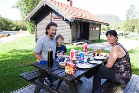 CAMPINGFERIE: Sandra Zabel (47), Torsten Zabel (52) og sonen deira Mattis (8) nyt frukosten utanfor hytta si. Familien frå Tyskland har budd ei veke på Jølstraholmen Camping. På fredag reiser dei vidare til Oslo.