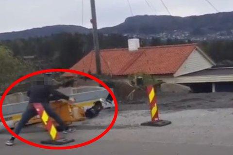 Her river mannen ned trafikklyset og knuser det.