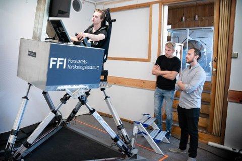 BYGDE SIMULATOR: Victor Urnes i simulatoren. Hans Anders Gjerland og Nikolai Grov Roald står på golvet.