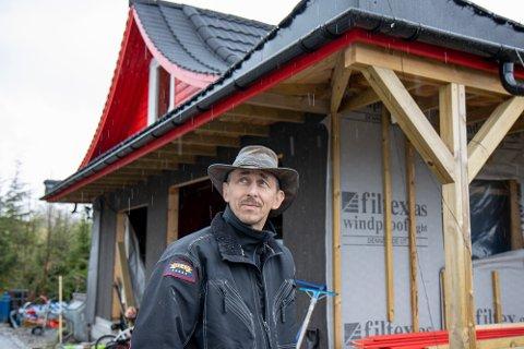 EIN HENDIG MANN: Pawel Zygmunt Szczesny er snikkar, og driv sitt eiget firma. På ein regnfull dag som denne kjem hatten godt med. I arbeid held den han i ly for regn, sol og vind.