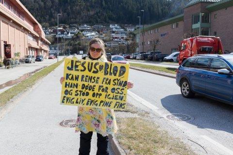 PLAKAT: Med denne plakaten stod ho foran bilkrysset i Førde. Ho meiner at det fins både ein himmel og helvete.