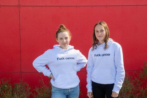 TYDLEG BODSKAP: Leah Grepstad og Frida Indrebø Birkeland  i genserane dei sel for å tene pengar til Kreftforeningen.