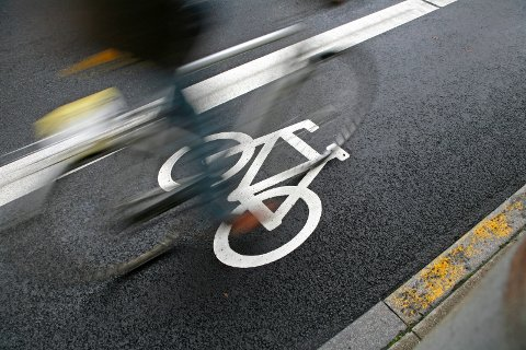 Cyclist passing by at an urban cycle path.