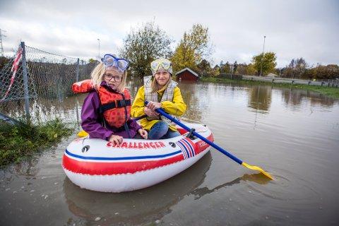 Alternativt fremkomstmiddel: Onsdag kunne ikke Emma Remine Bergstrøm (til høyre) gå hjem fra skolen fordi undergangen og veien var oversvømt. Hun måtte hentes av moren og lillesøsteren Mia Sofie Bergstrøm (5). Gummibåten illustrerer hvor mye vann det er.