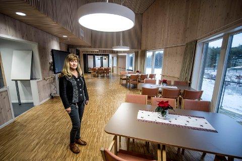Lise Krogstad i det nye dagsenteret  på Dypedalsåsen. Det er parkett på gulvet og mye trepanel på veggene.  I neste rom er det  snekkerverksted med egen høvelbenk.