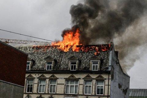 TOTALSKADET: Det tok ikke lang tid før flammene nådde gjennom taket i toppetasjen på gården. Arkene er revet på grunn av rasfare, og ifølge gårdeieren er det bare etasjeskillene som holder fasaden på plass.