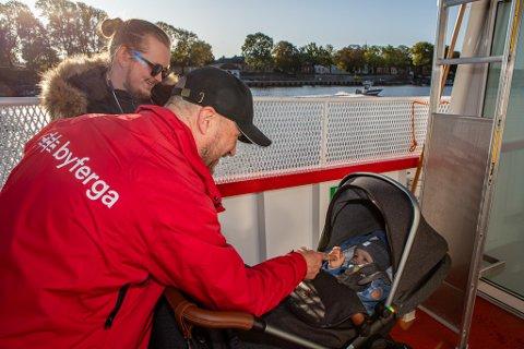 FØRST: Julian Levi (11 måneder) og pappa Jonas Olsen ble de første som fikk være med om bord i den nye elferga. Her får passasjer nummer en en «high five» av Dag Runde.