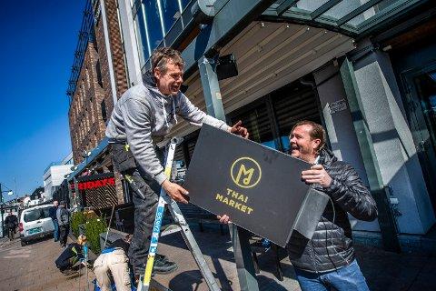 Terje Olsen (til høyre), deleier av Thai Market, er godt fornøyd med utviklingen i restauranten etter at den flyttet fra Stortorvet til Brygga. Lars Erik Iversen ska herl montere nytt navneskilt.
