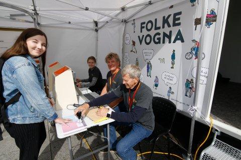 Forhåndsstemmer: Thea Karlsen forteller at stemmelokalet Folkevogna passer henne utmerket. Valgfunksjonærene Asbjørn Borge (nærmest), Steinar Haugsten og Marie Eriksen. (Foto: Svein Kristiansen)