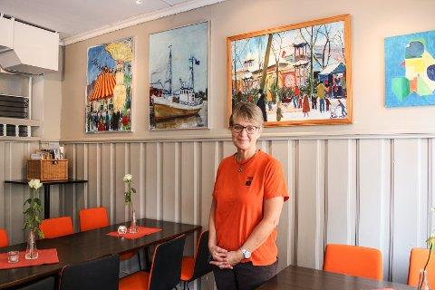 GLAD: Leder på Café Britannia, Anne-Marie Kvarme, seter stor pris på at kafeen fylles av kunst. – AT vi i tillegg får inntektene fra salget er vi veldig glad for, sier hun.