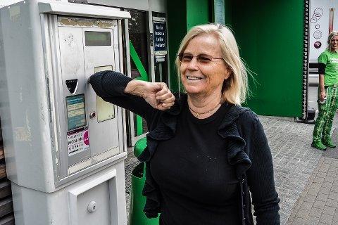 Anne Kristin Bø har sin egen variant av smittesikker betjening av parkeringsautomaten utenfor Kiwi på Skjærhalden, en butikk hun føler seg ekstra trygg i.