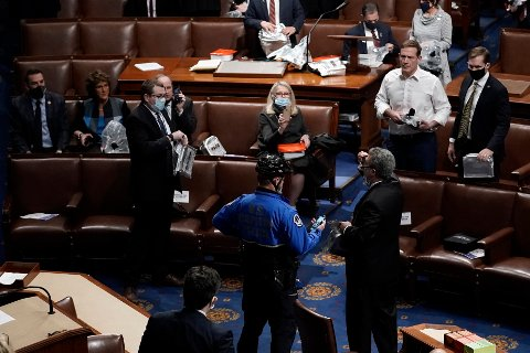 Lawmakers prepare to evacuate the floor as protesters try to break into the House Chamber at the U.S. Capitol on Wednesday, Jan. 6, 2021, in Washington. (AP Photo/J. Scott Applewhite)