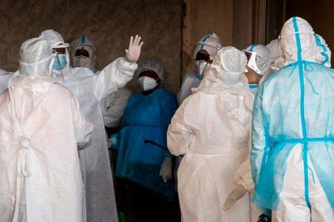 Angolanske helsearbeidere iført smittevernutstyr blir desinfisert etter å ha utført korona-tester på flypassasjerer på Den internasjonale flyplassen i Luanda. I februar påviste de en helt ny variant med hele 34 mutasjoner. Foto: Osvaldo Silva (AFP)