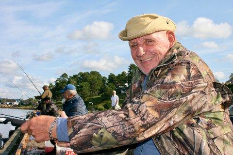 FIN HOBBY: Pensjonist og hobbyfisker Jan Madsen (67) koser seg med makrellfiske i solsteken på brygga i Høysand. Foruten bra med fisk får de som holder til der også en god dose med humor i løpet av økta.