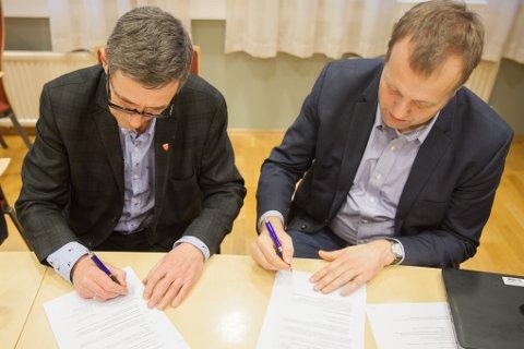 Steinar Sørensen (til venstre) og Arne Quist Christensen i Telenor setter sine signaturer på avtalen om bredbåndsutbygging i Evenes.