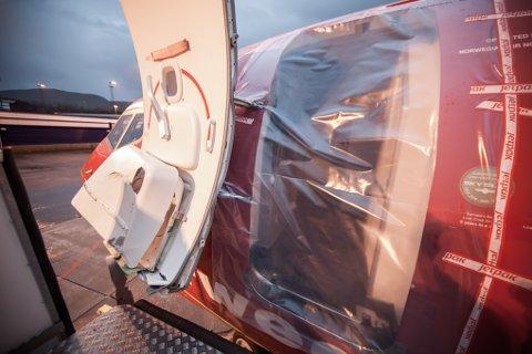 Den fremre inngangen til Norwegian-flyet er dekket til med plast, etter at flytrappa blåste over ende og skadet døren på flyet.