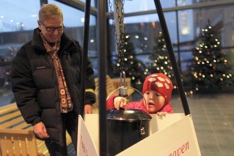 Arkivfoto fra et tidligere år. På bildet er det Inis Ivarsson og barnebarnet Amalie Ivarsson Elverum som donerer til julegryta.