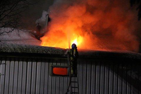Flammene står opp av taket på huset. Brannen startet trolig i garasjen og spredte seg til bolighuset i Beisfjord.