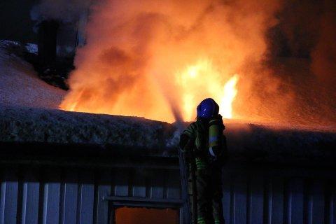 Flammene står ut av taket i bolighuset som brenner i Beisfjord