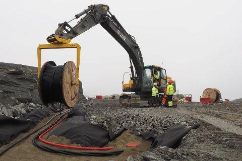Kilometervis med kabler legges omhyggelig ned i bakken, beskyttet av duk og spesiell kabelsand.