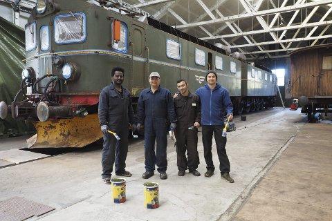 Klar til maling: I flere måneder har Jonas Tesfamichael fra Eritrea, Jamal Mohammed og Jihad Jimo fra Syria jobbet sammen med Martin Framnes med å restaurere lokomotivet. Nå går de i gang med malingen. Foto: Ann-Kristin Hanssen