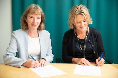 Sonja Berlijn, FoU-direktør i Statnett, og Ingrid Schjølberg, dekan på fakultet for informasjonsteknologi og elektroteknikk på NTNU, signerer samarbeidsavtale om cyber security.