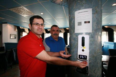 SPRITING OG FEBERMÅLING: Huseyin Demir og Huseyin Tasci ved Bella Napoli i Narvik har tatt smittevern på alvor når de tilbyr gjestene handsprit og febermåling når de kommer inn i restauranten.