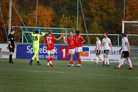 BLE KLAR: Mathias Nicolaisen, Mjølners kaptein i midten blant spillerne med rød drakt. .