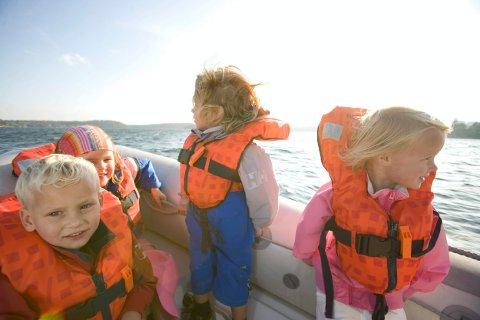 TRYGGE BARN: Redningsvester er et must i båt. Noen ganger kan det også være lurt å ha redningsvest når man ferdes på stranda, eller langs bryggene. (Arkivfoto).