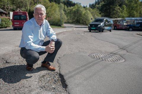 SLAGHULL: Asfalt som ødelegges slik at det etterlater slaghull, fører også til grus i veibanen. Kommunikasjonssjef i Gjensidige, Arne Voll, viser et eksempel.