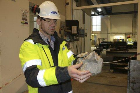 Fabrikksjef Johnny Reiestad viser fram steinen som gikk gjennom taket og landet i produksjonshallen helt i slutten av februar.