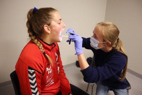 Medisinstudent Emilie Stendahl sjekker om Elise Pedersen har symptomer før hun får spille håndball.
