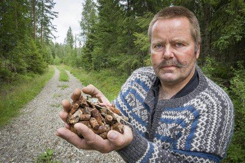 UTMARKSOPPSYN: Bjørn By er redd for dyr og mennesker som ferdes områd   et, han sier flere har sluttet å bruke skogsveien på grunn av veidekket. På bildet holder By opp ruste batterier og metallrester fra veidekket. Foto: Jens Haugen