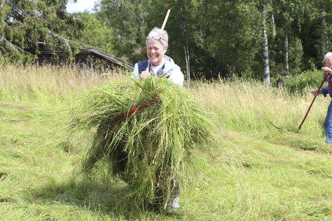 MOT HØYHEKKEN: Eneste kvinne i åkeren på bygdetunet var Kjersti Haug, som hadde taket på riva og graset.