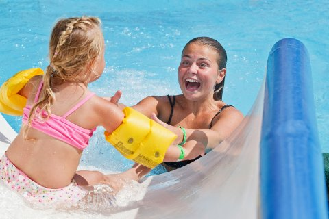 Maja Sofie Mjøs (15) er fra Bergen og er i lekelandet sammen med sine slektninger. Her tar hun i mot sin niese som kommer i fin fart ned den store vannsklia.