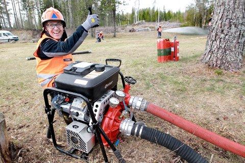 FORNØYD: Pumpefører i Sivilforsvaret, Roger Svensrud, er strålende fornøyd etter å ha fått liv i den nye pumpa, og sendt vann ut i strålerørene til mannskapet i bakgrunnen.