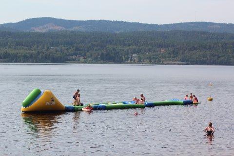 FLYTENDE BADELEKE: Det er mange som tar i bruk den flytende hinderløypa ute i vannet.